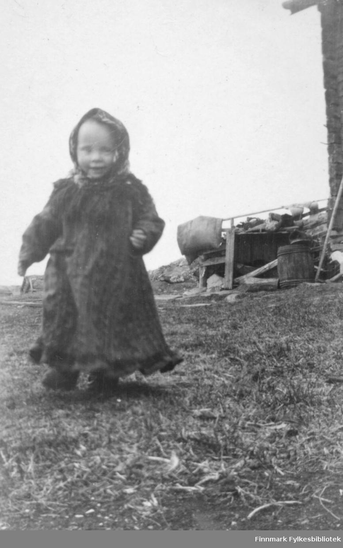 Fotografi av en liten jente kledt i en lang kjole eller en sommerkofte. Rundt hodet har hun et sjal. Til høyre ser man litt av et hus. Det står en tretønne på bakken