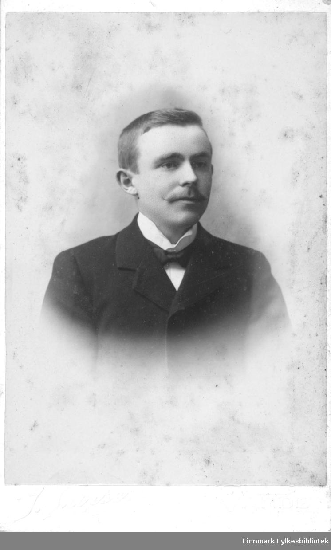 Portrett av en ukjent mann med bart. Han er kledt i en mørk jakke og hvit skjorte. I halsen har han en tversoversløyfe