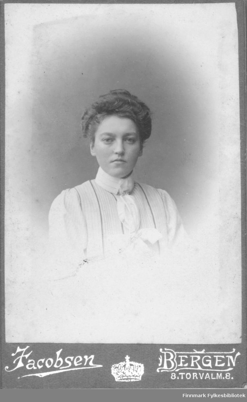 Portrett av ei ukjent kvinne. På bildet er hun kledt i en lys bluse eller kjole. Hun har en hvit sløyfe som pynt. Håret hennes er oppsatt