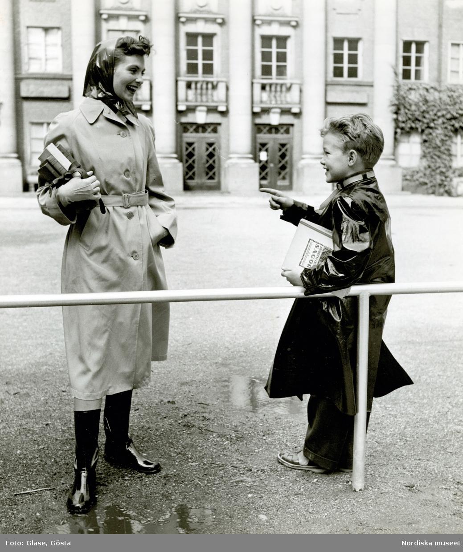 Kvinna i kappa och sjalett med böcker i handen bredvid pojke i regnrock, utanför byggnad.