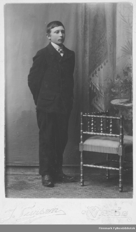 Portrett av en ung menn kledd i en mørk dress og hvit skjorte. Studio ateliere teppebakgrunn gardin. stol i messing stikker inn i bildet.  Albumet med bildet kommer fra Ekkerøy, kanskje han kommer derfra.