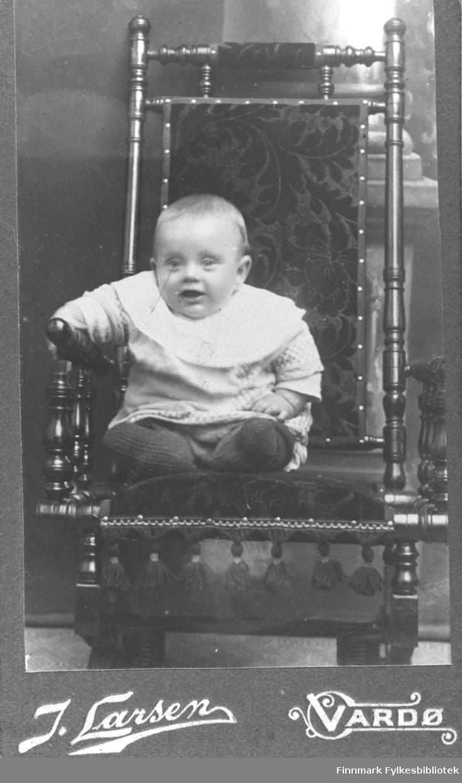 Lite barn som sitter i en stol i studio ateliere.  Albumet med bildet kommer fra Ekkerøy, kanskje barnet bodde der.