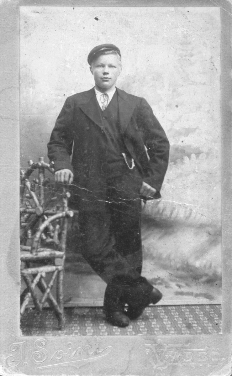 En ung gutt lener seg til en stol på et fotostudio. Han er kledd i dress: jakke, vest, bukser og et lommeur. Han har også på seg en hatt. Portrettet muligens tatt på slutten av 1800-tallet eller begynnelsen av 1900-tallet.