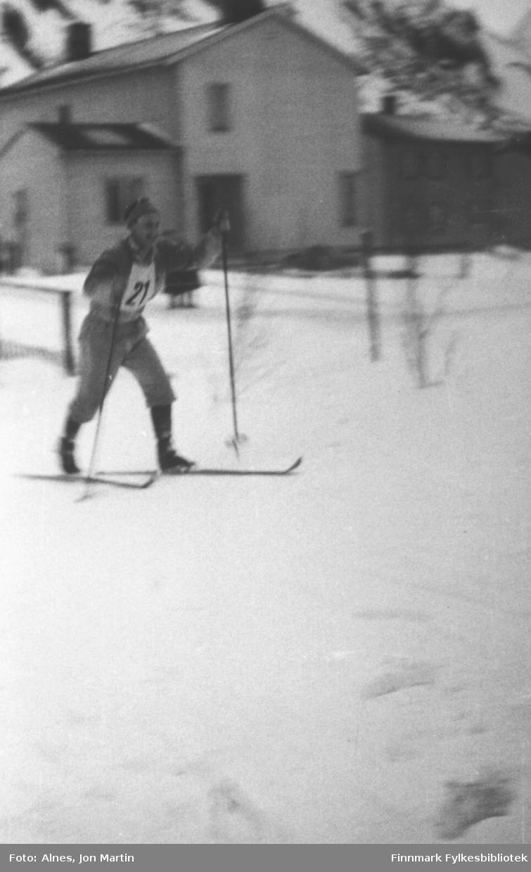 Skirenn i Øksfjord i 1954 - Arvid Thomassen som startnummer 21. Løypa gikk rundt i bygdas sentrum. Bygningen i bakgrunnen: Disponentboligen, som i dag eies av Gunnar Olafson