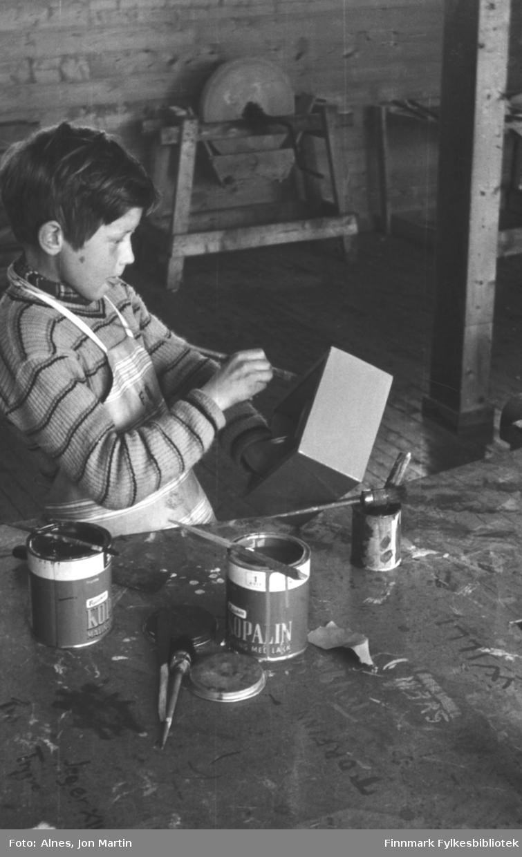 Tunga rett i munnen! Gunnar Pettersen maler kista han laget på sløyden i 4. klasse på Øksfjord barneskole i 1954