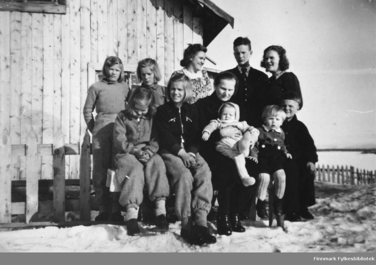 """Gruppebilde av familien Stenbakk. Under bildet står det  at """"far selv er ikke med"""" (på bildet). Fotografert på Stensbakk, 1948."""