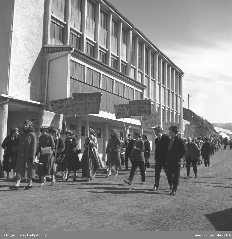 Grønnrussen er på tur ned Skolebakken utenfor den nybygde Breilia ungdomsskole. Flere festkledte mennesker følger bak.