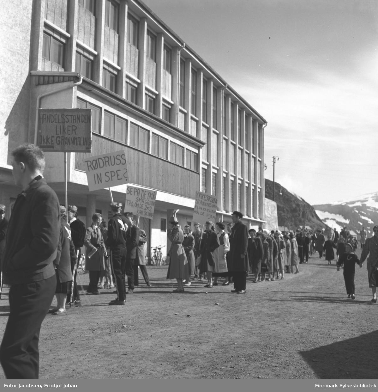 Grønnrussen har stilt opp i Skolebakken utenfor den nybygde Breilia ungdomsskole. Flere festkledte mennesker følger bak.