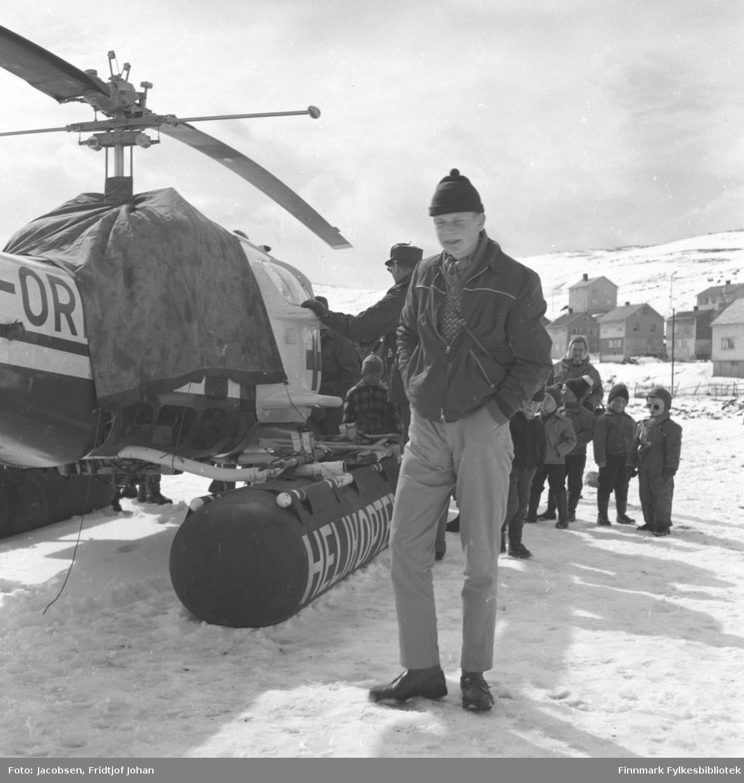 Arne Jacobsen står ved siden av et helikopter fra Helikopter Service A/S på Hammerfest stadion med noen barn bak han. Bebyggelsen i Skytterveien ses i bakgrunen.