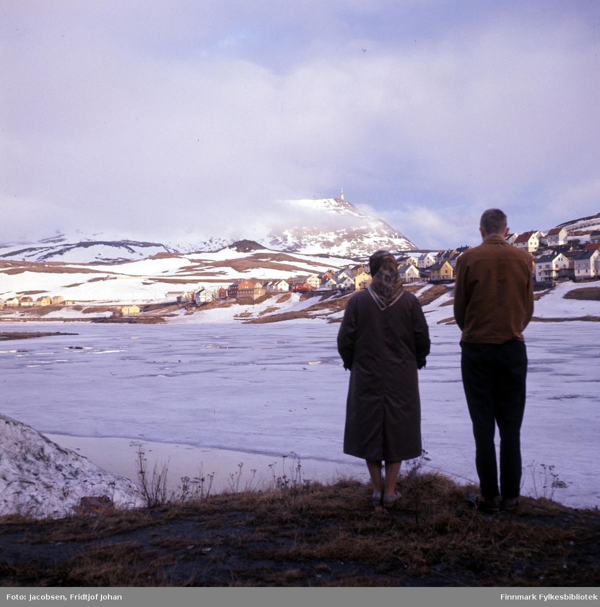 Aase og Arne Jacobsen står ved bredden av det islagte Storvannet. Fjellet Tyven med TV-masta ses såvidt mellom skyene.
