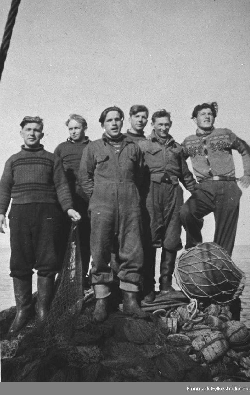 Seks menn står på fiskegarnutstyr og not ved havet. Fra venstre: Karl Gærnæ, Frants Kandola, Hans Gærnæ, Anton Gærnæ, Ludvik Nikuma og Sverre Jakola. Mennene har arbeidsklær og støvler på seg. Karl Gærnæ holder not på handen, det ligger en stor garnblåse på fotan til mennene. Bak gruppen ser vi havet.                       På bakgrunn ser vi et par fiskebåter til, deler av kaien og byggninger, et av dem Rosets Hus.  den.