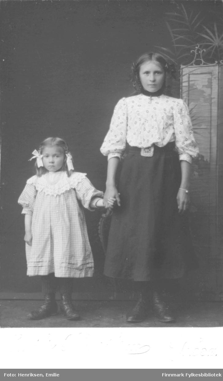 Gruppebilde av to jenter, navn ukjent. Jentene står hånd i hånd foran en malt landskapsbakgrunn, begge har flettet hår. Den største jenta har en mønstrete bluse og mørkt skjørt, med belte i livet. Hun har et armbånd med en kule på ene håndleddet og et stort kors (smykke) i halsen. Den minste jenta har rutete kjole med stor blondekrage og perlesmykker i halsen. Begge har snørestøvler på bena. Bildet er tatt av Emilie Henriksen i Vadsø. Jentene er sannsynligvis søstre fra Vadsø.
