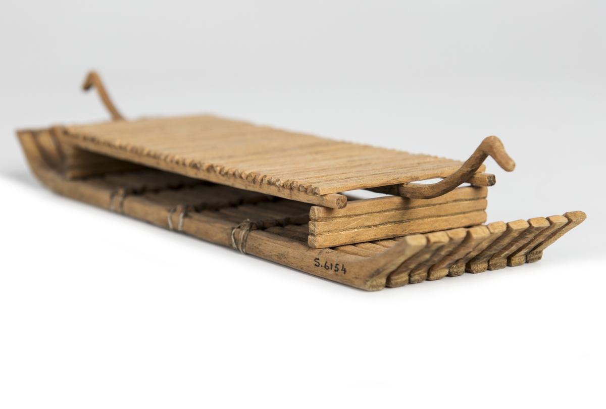 """Modell av flotte, rekonstruktion av """"Bredarötypen"""", skeppsbild från Bredarör invid Kivik, Skåne. Flytkropp av 9 raka, i ändarna svagt uppböjda stockar, sammanhållna av 3 tvärbalkar och två plattforms stöttor. Plattformen består av tvärgående ribbor uppburna av tre längsgäende spärrar varav den mittersta, utskjutande, avslutas med djurhuvud. Skala: 1/60 (Jfr. S.5892 = skala 1/50)."""
