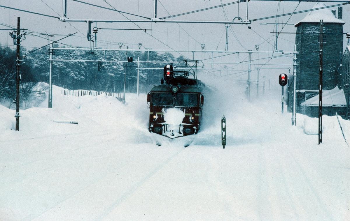 """Ekspresstog 42 """"Dovreekspressen"""" med lokomotiv NSB type El 14 kjører inn på Oppdal stasjon. Bildet er tatt fra lokomotivet i nordgående kistog Hjerkinn - Marienborg."""