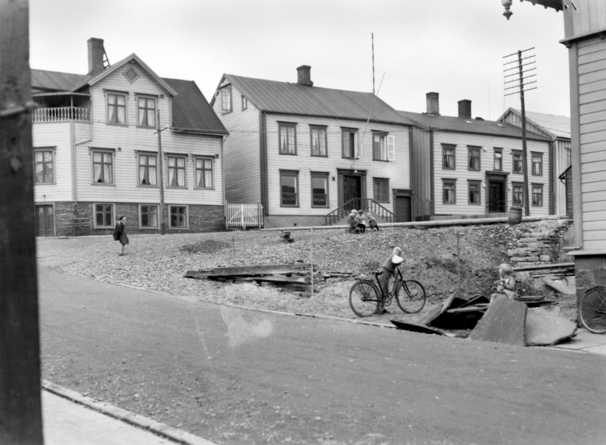 Fotografi fra Vadsø med Vadsø Sparebank som  ble etablert i 1853. Banken hadde banklokale og bolig for bankkassereren i Theatergaden,  i huset midt i bildet. Til venstre sees Kildahl Olsens bokhandel. Til høyre står huset som var eid av Esbensens arvinger og som senere ble solgt videre til jordmor Anna Andreassen. Helt til høyre i bildet sees et hjørne av Kommunehuset (tidligere Vestre folkeskole), der også folkebiblioteket holdt til.