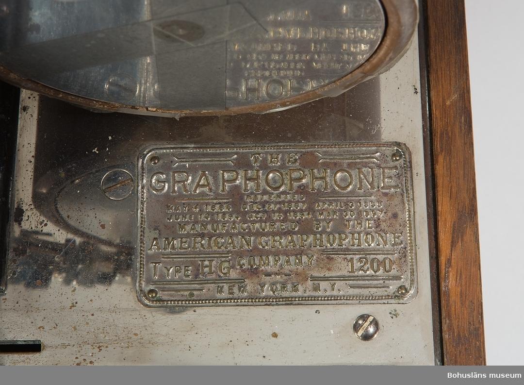 Uppgifter ur punktnummerkatalogen 1957-1976: Ljust brunbetsat trä. På huven text i svart och guld: The GRAPHOPHONE, patented May 4 1886. Dec. 27, 1887. April 3, 1888. June 10, 1890. Oct. 15, 1894, March 20, 1897. Sears, Roebuck & Co. Inc. Cheapest supply house, Chicago, Illinois. (Sears var ett amerikanskt handelsbolag grundat 1893 som bl.a. producerade varukataloger.)  Apparaten av stål. Skylt med text: American Graphophone Company, Type HG 1200, American Graphophone Company New York N.Y. Vaxrulle och vev m.m.