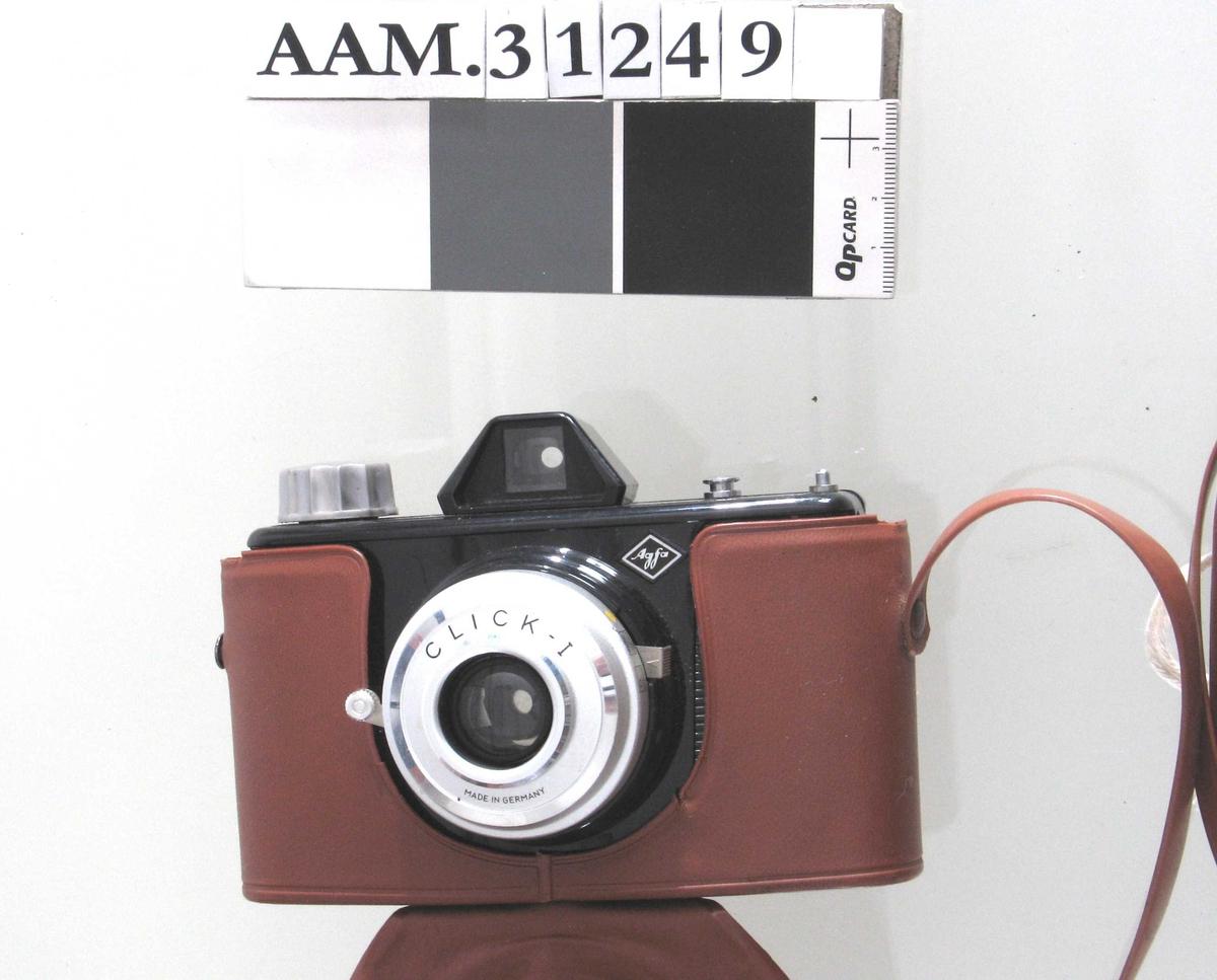 Sort kamera i brunt, todelt plastetui. Delen foran kameraet kan vippes frem, er festet med skrue under bunnen og trykknapp bak. Blitz i eget etui, som har glidelås og er festet til hals-reima.