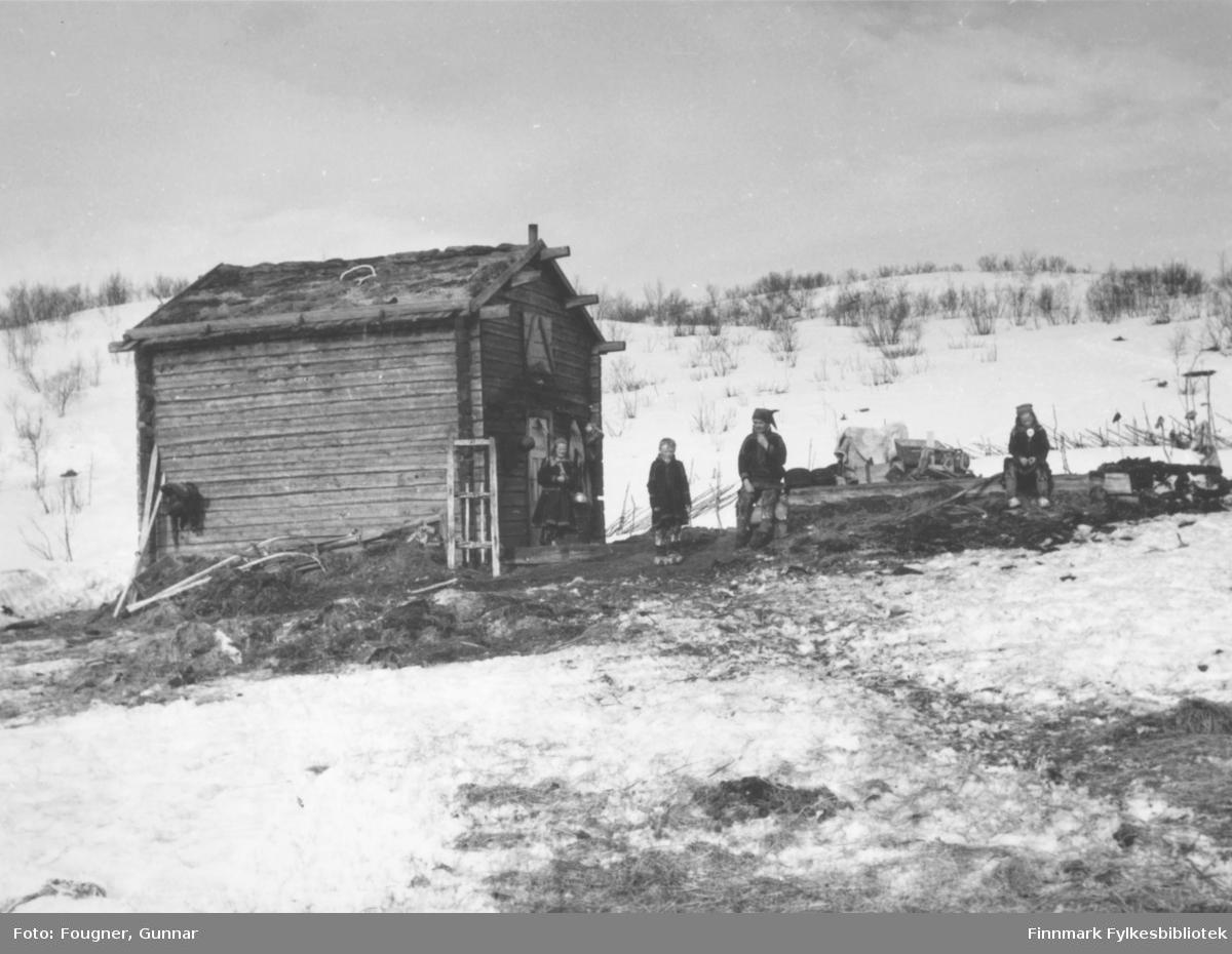Fire samer, en mann og tre barn, utenfor boligen sin, en hytte av laftet tømmer.
