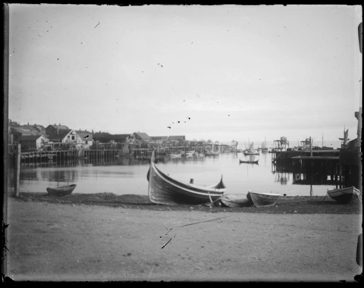 Båter trukket opp på Valen i Vardø. I bakgrunnen kaier og pakkhus, båter på Søndre våg