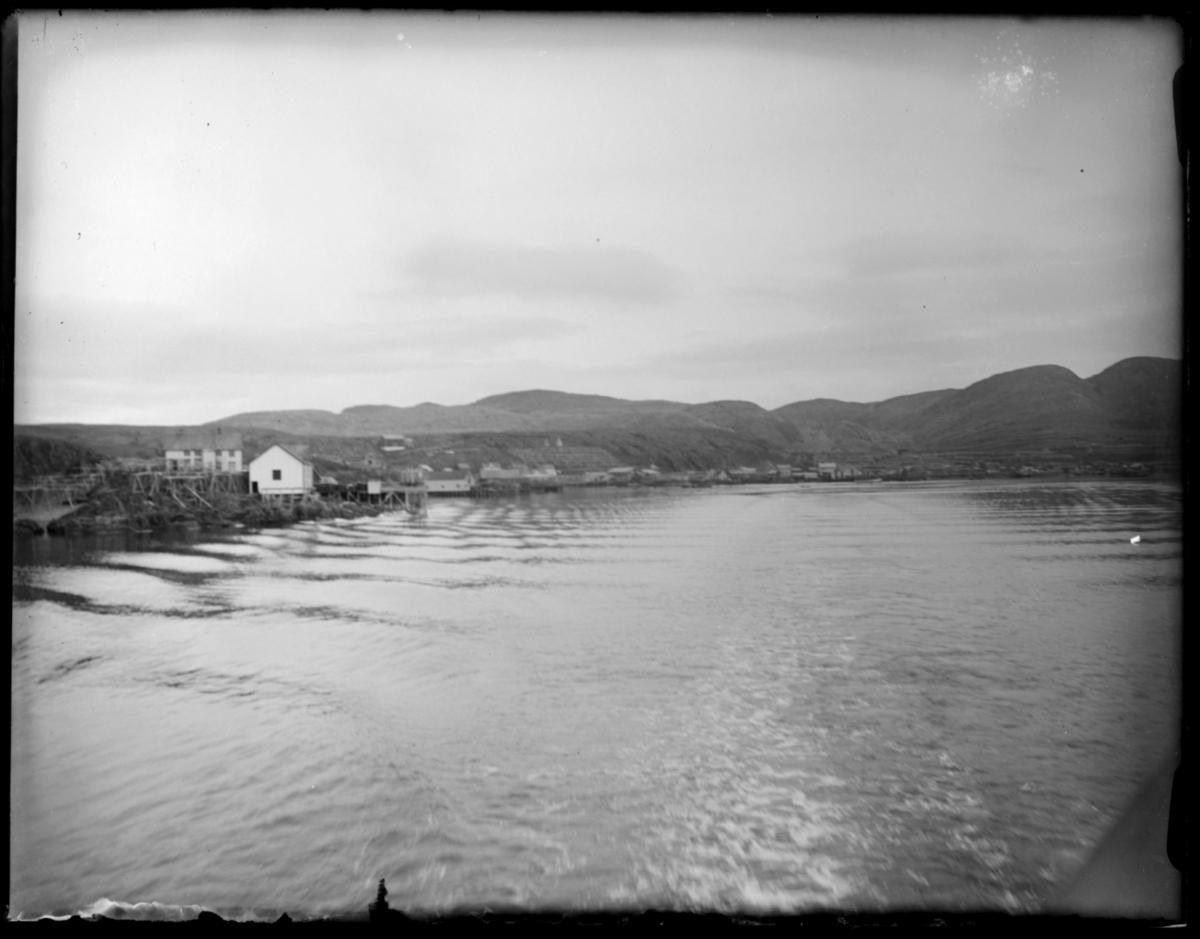 Bildet er tatt fra båt. Viser kystlandskap med lave fjell, og et ukjent fiskevær med små hus, sjøboder, brygger og tomme fiskehjeller.  Kanskje fra reisen nordover i 1912