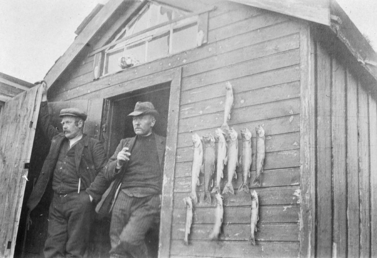Blåsenborg 1915. To menn i døråpningen. Fisk henger på veggen.