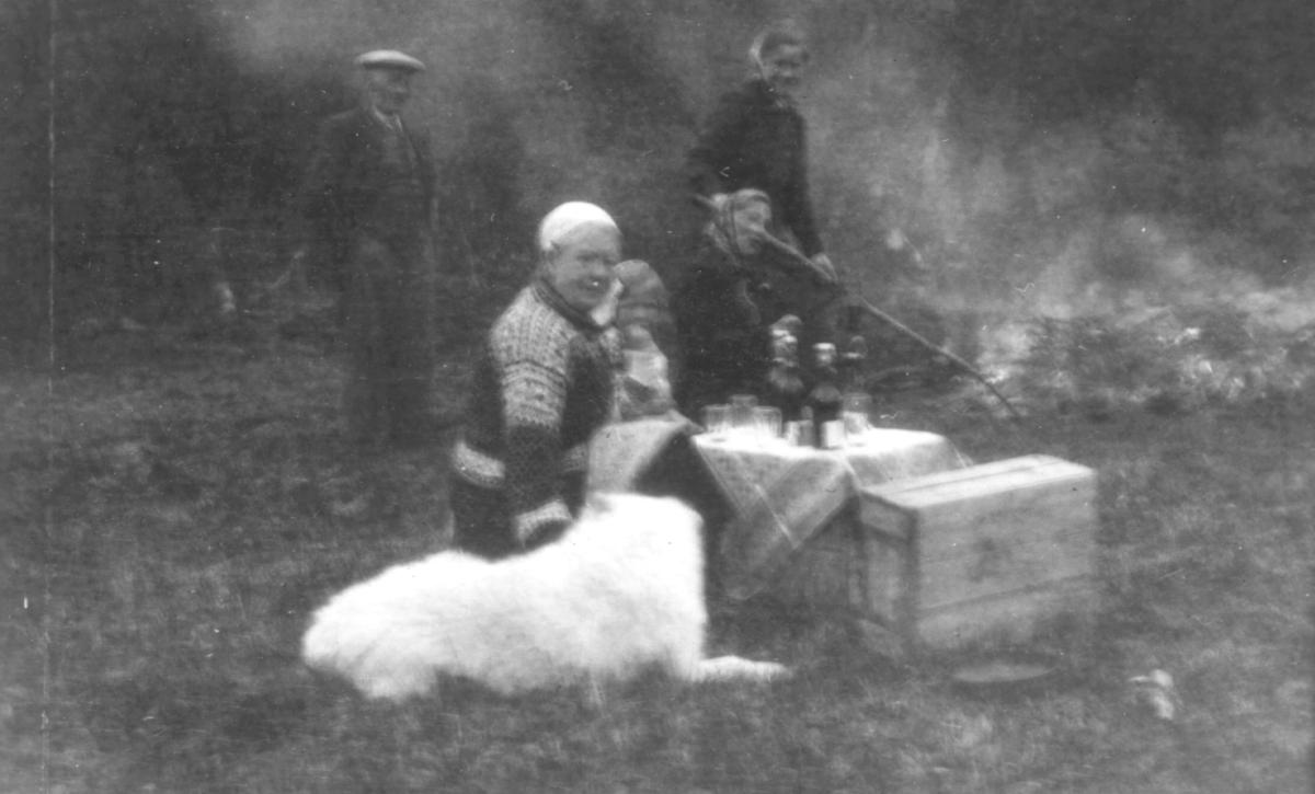 To damer og en liten pike sitter ved et bord. En kasse står ved siden av.Foran ligger en lys hund. På bordet står det flasker og glass. Bak står en dame med en stokk og roter i et bål. En mann står til venstre.