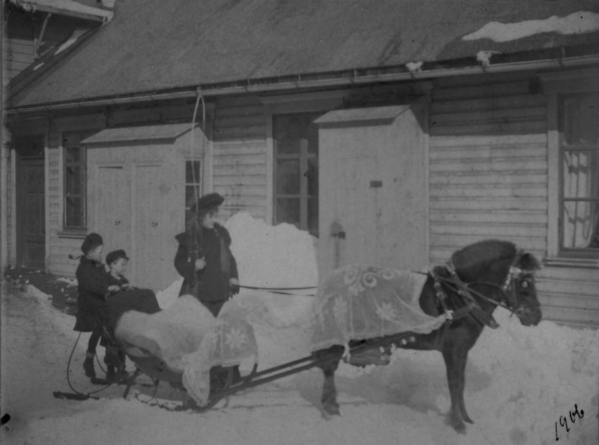 En hest(Tommeliten) med sitt herskap. To barn sitter bak på sleden. En dame ved siden av. Det er snø på bakken.