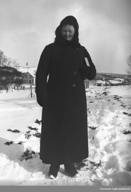 Kathinka Mikkola kledd i mørk vinterkåpe og skinnlue. Hun har salmeboka under armen. Bildet er tatt ved kapellet i Neiden i anledning en begravelse. Langs veien ligger einerkvister, kanskje i anledning begravelsen