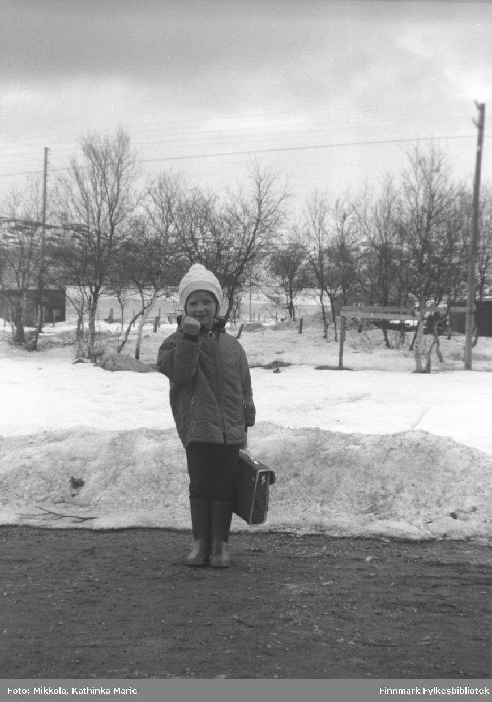 Anita Lindseth med skoleransel i veikanten i Bugøyfjord. Hun hytter med neven mot fotografen! Bildet er tatt ved samme anledning som 05007-244