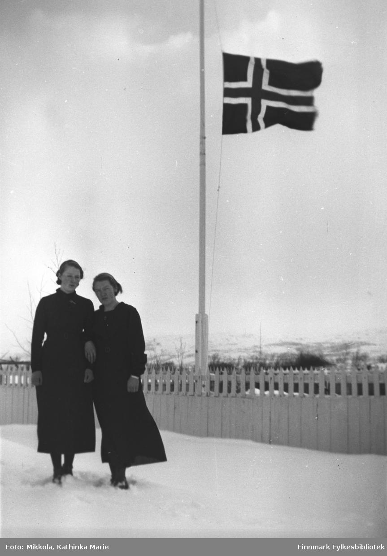 Marine og Synnøve Mikkola i svarte kjoler i snøen på Mikkelsnes. Bak dem vaier flagget på halv stang. Bildet er tatt på begravelsesdagen til jentenes bestemor, Sofie Josefine Mikkola, mor til Aksel Konrad. Hun døde i 1937
