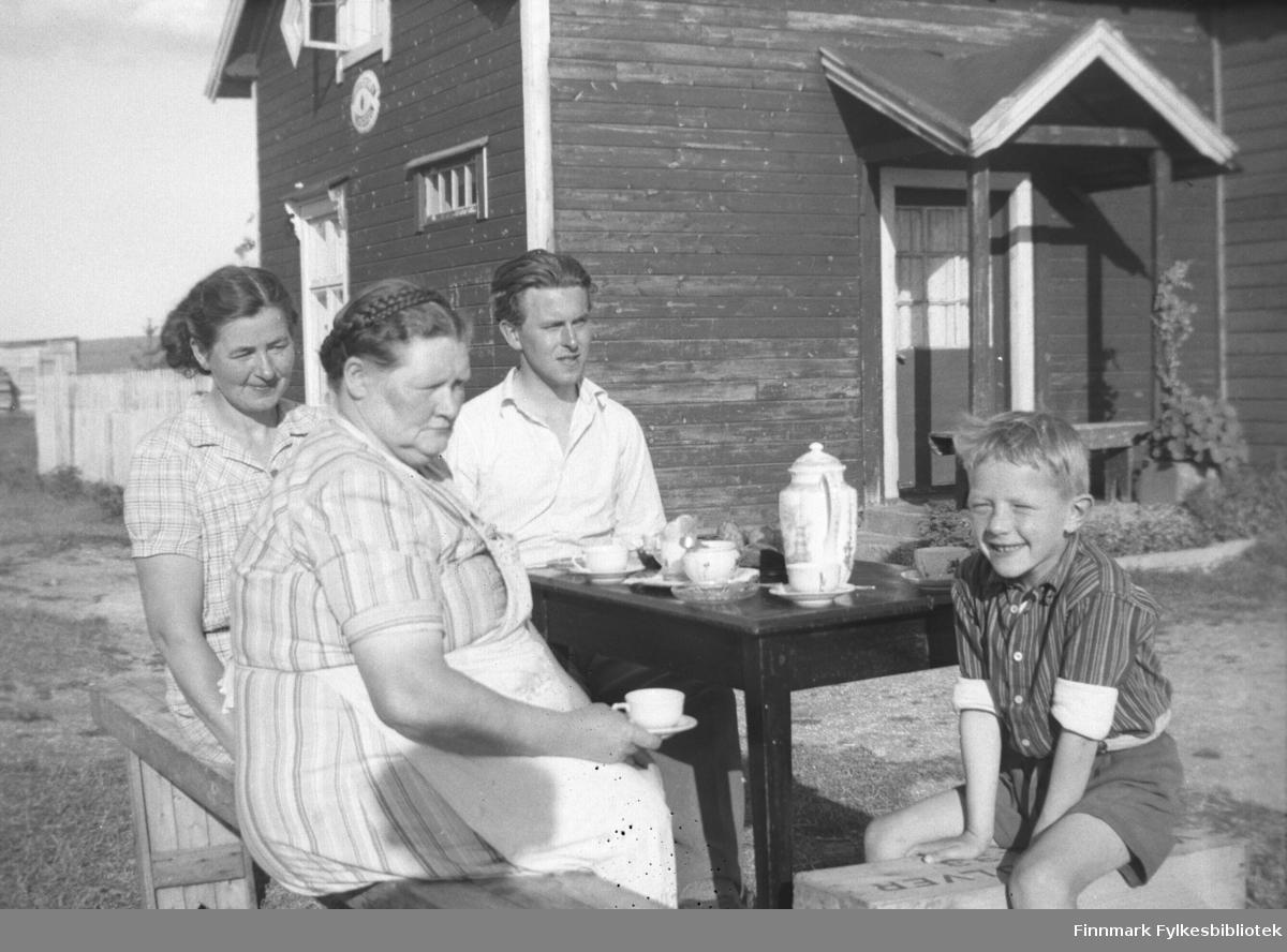 Ukjent par på besøk på Mikkelsnes, ca. 1947-1949. Her sitter de ute og drikker kaffe. Merk talestasjon-skiltet på veggen på våningshuset i bakgrunnen. Kathinka Mikkola sitter med kaffekoppen i handa. Barnebarnet hennes, Per Olsen, sitter til høyre og smiler mot fotografen