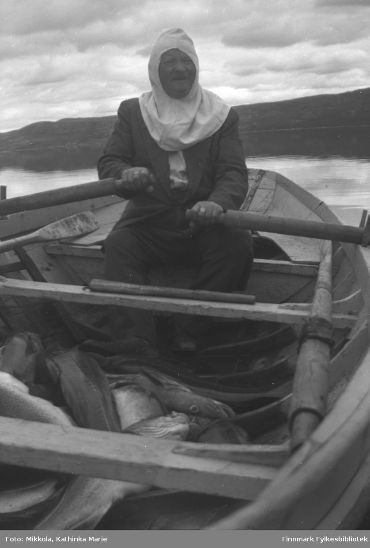 I fjæra ved Mikkelsnes. Aksel Konrad Mikkola har vært på sjøen og har fått fin, stor torsk. Her sitter han i akterenden med mygghette og årer. Ett av rommene i båten er fylt av fisk