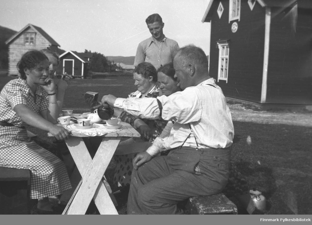 Kaffe utendørs på Mikkelsnes, ca. 1950. På venstre side av bordet: Astrid Mikkola d.e., Marine Mikkola. På høyre side av bordet: Aksel Konrad Mikkola, Ida Mathisen fra Munkefjord og Kathinka Mikkola. Storm Mikkola ser smilende på Kathinka, som betrakter en kubjelle
