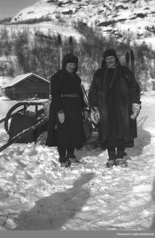 Vinterkledde kvinner i snøen på Mikkelsnes. Til venstre Kathinka Mikkola i samekofte og med en solid skinnlue på hodet. Hun har fine strikkavotter og et samisk vevd belte om livet. Til høyre Amanda Olsen Lie i pesk og skinnvotter, hun har også skinnlue. Begge har skaller. Bak dem står en stabel pulker og sleder, to par ski står oppreist i snøen. I bakgrunnen et uthus av tømmer