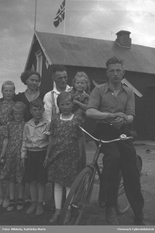Gruppebilde tatt utenfor våningshuset på Mikkelsnes, ca. 1936-1938. Bak fra venstre: Gudrun Mikkola, så en kvinne som var søster til Oskar Nilsen og hennes mann med Herlaug Mikkola på armen. Vi vet ikke navnene på ekteparet. Foran: Astrid Mikkola, en ukjent gutt, Ingrid Mikkola. Storm Mikkola sitter på sykkelen. Alle barna er pent kledd, og det flagges på gården. Bildet kan være tatt i forbindelse med en 17. mai