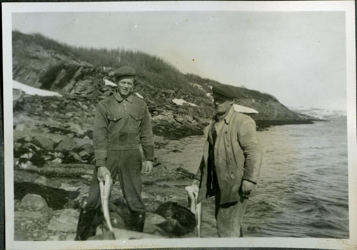 Ukjente menn viser fram fangsten etter fiske. Mennene er kledd i jakker bukser, støvler og luer. De er trolig tilknyttet (muligens arbeidere på) skiferbruddet i Friarfjord.I bakgrunnen kan man se skiferstein langs vannkanten.