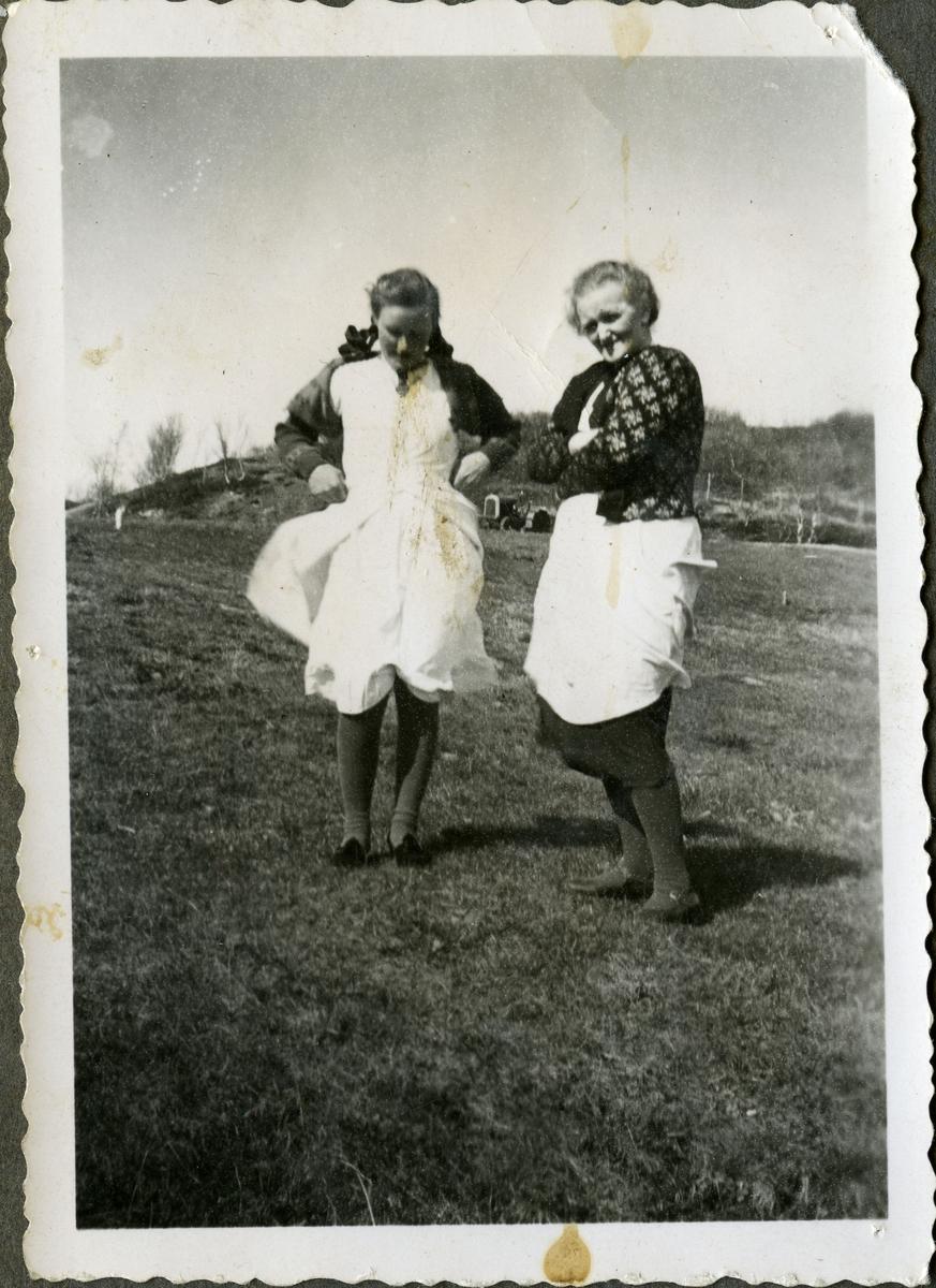 Fra venstre: Åse Reeberg og mor Anna Reeberg. Anna er kledd i strikket jakke med mønster, forkle og kjole. Åses kjole blir tatt av vinden. Hun har fletter og sløyfer i håret. I bakgrunnen, mellom damene, kan man se en traktor.