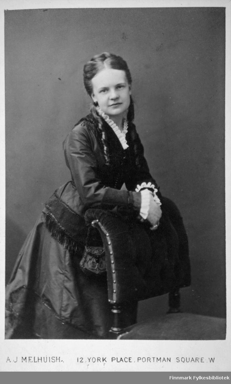 Portrett av en dame i et mørk kjole. Hun har en hvit krage rundt halsen og hvite border rundt håndleddene. Hun står litt foroverbøyd og lener seg mot en stolrygg. Portrettet er tatt hos fotograf Arthur Melhnish i London.