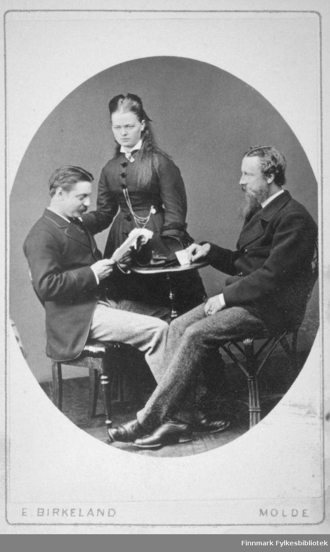 Portrett av tre personer, to menn og en kvinne. Mennene sitter på stoler og kvinnen står.  Mannen til venstre på bildet har en mørk dress jakke og en lysere bukse på seg. Damen i midten har en mørk kjole på seg og noen kjeder henger foran på kjolen. Mannen til høyre på bildet har en mørk dress og hvit skjorte. Portrettet er tatt ved E. Birkeland atelier i Molde.