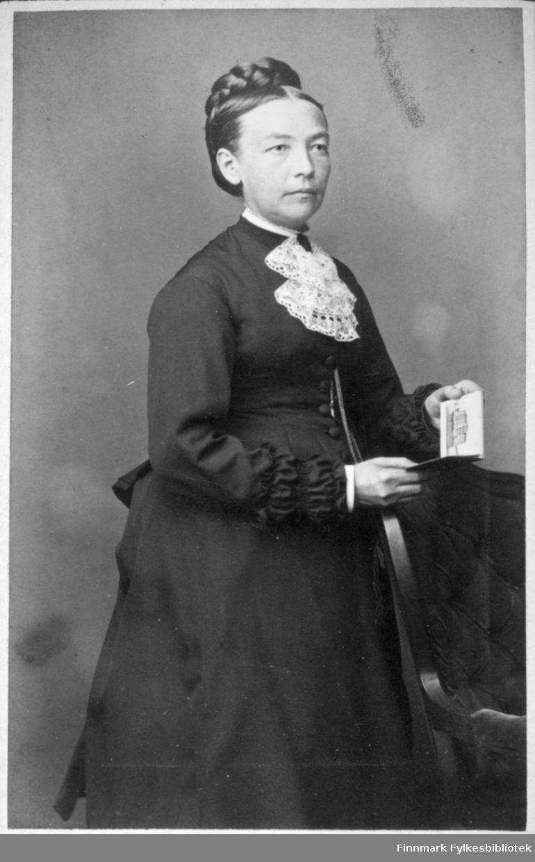 Portrett av en dame i en mørk, sid kjole. Hun har et hvitt, helket tøystykke hengende rundt halsen. Hun holder en liten bok/hefte foran seg. Portrettet er tatt hos Meyer & Nicolaysen i Bergen.