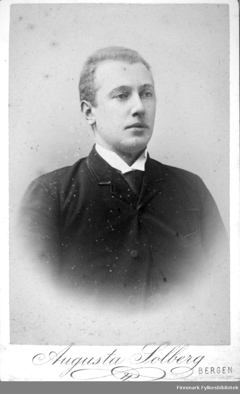 Portrett av en mann iført en mørk dress. I halsen stikker den hvite skjortekragen fram under dressjakka.