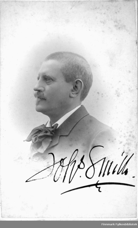 Portrett av en mann i mørk dressjakke og hvit skjortkrage med en stor sløyfe i halsen.