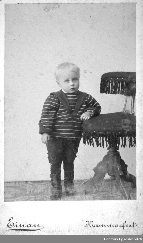 Portrett av en lyslugget gutt. Han har mørke bukser og sko på seg. Genseren er også mørk med lyse striper. Et skjerf eller noe lignende er knytt rundt halsen. Han støtter seg med venstre armen på en stol med frynser og fot med utskjæringer. Gulvet har belegg med sirkel- og heptagonmønster.
