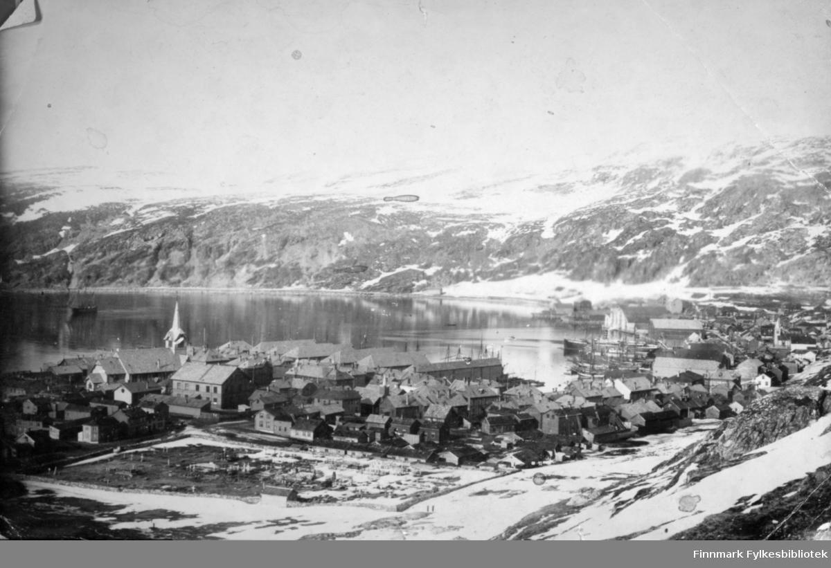 Hammerfest fotografert fra Salsiden. I forgrunnen ses kirkegården. Kirka med tårnet ses litt til venstre på bildet. Mange båter ligger ved kai i havna og tak på store pakkhus/havnebygninger ses langs kaikanten. Boliger ligger rundt kirkegården i bydelen Haugen. En del boliger ligger også i Salsiden. På andre siden av havna ses Fuglenesveien ved foten av Mollafjell og Fuglenesfjell og ute på fjorden ligger et fartøy. Noe snø/snøflekker i terrenget som tyder på at blidet er tatt på våren.