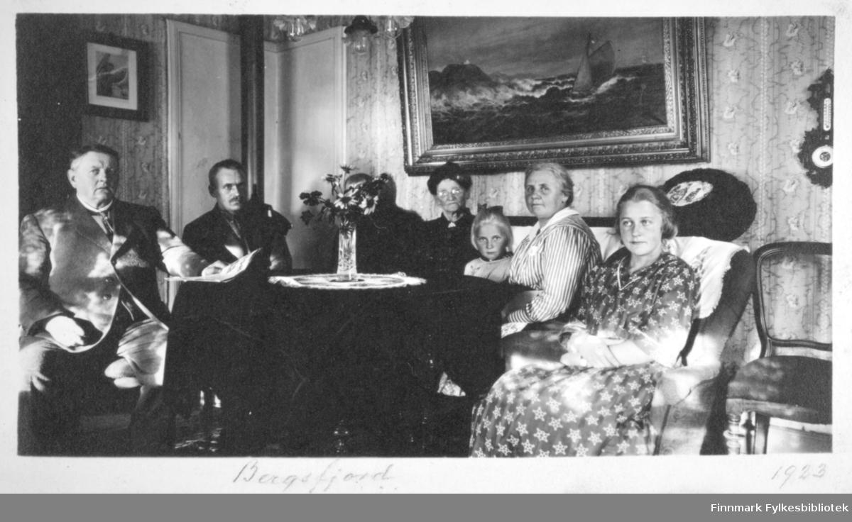 Flere personer sitter rundt et bord, fra venstre: Cort Buck, tre ukjente, Ester Buck, Theodora Buck og Cecilie Buck Rustad. De to til venstre på bildet, en med dressjakke på seg, sitter i stoler. De to damene, med Ester Buck mellom seg, sitter i en sofa og helt til høyre sitter Cecilie Buck i mønstret kjole. Bak henne står en rund sofapute. Helt til høyre står en lenestol og et barometer henger på veggen over den. På det runde bordet står en blomstervase av glass med en liten bukett oppi. En mønstret duk ligger på bordet og og en liten del av en lysekrone kan skimtes helt øverst på bildet. På veggen bak damene henger et stort maleri og på veggen til venstre henger et fotografi. Stuen har stripet tapet med blomster på veggene.