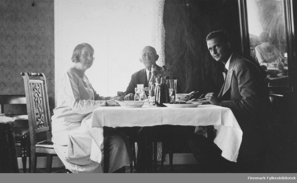 Tre personer, en kvinne og to menn, sitter ved et bord på hotellet i Bossekop. Damen til venstre på bildet er Gerda Buck. Hun har lyst helskjørt og sitter på en stol med utskjæringer på ryggen. Mennene har mørke dresser, skjorte og slips. I midten sitter Hans Ulich som er på norgesbesøk fra USA. En hvit duk ligger på bordet og oppå står kopper og glass, fat, et liten brødkurv, en flaske og en sort kanne. Til høyre henger et stort speil på veggen og midt på bildet er et vindu med lyse, hvite gardiner. Veggene har tapet med vertikalt mønster.