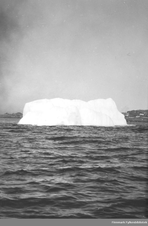 Et isfjell flyter i sjøen. Mye store og tette, men hvite skyer på himmelen. Små bølger på sjøen tyder på lite vind. Bak isfjellet ses et fjellparti med noen snøflekker og som ender i et nes helt til venstre på bildet.