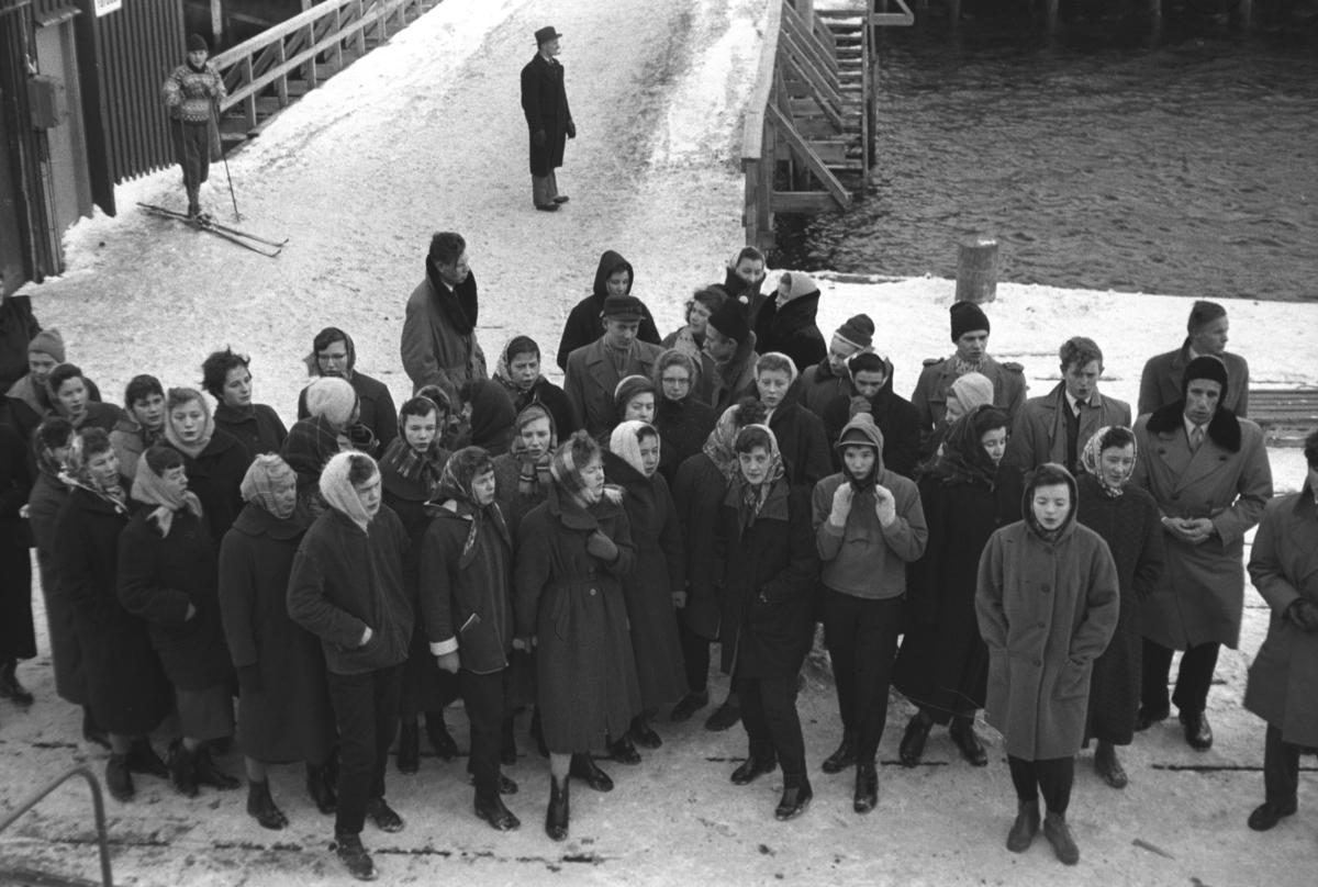 En folkemengde er møtt fram på kaia når Hurtigruta leegger til. Iflg. informanten kan stedet være Havøysund.