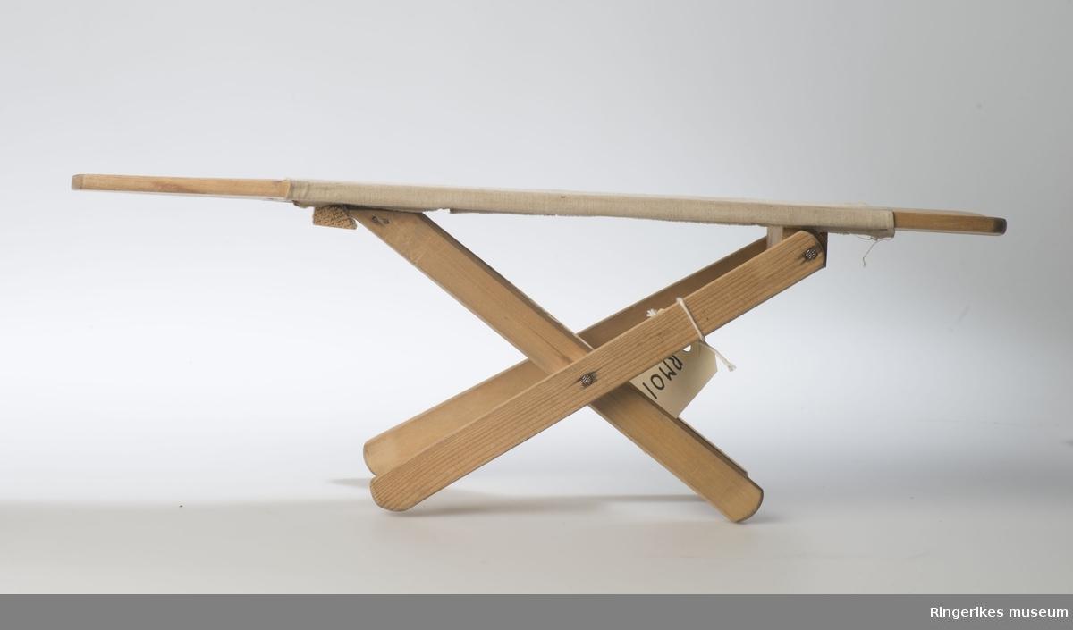 Rektangulært brett med skrådde flater i en ende, montert på stativ som kan reguleres til stående eller liggende . Går i kryss når det settes opp.Brettet tekstil på tvers. Tverrstilt list på undersiden som regulrer stativet til stående.