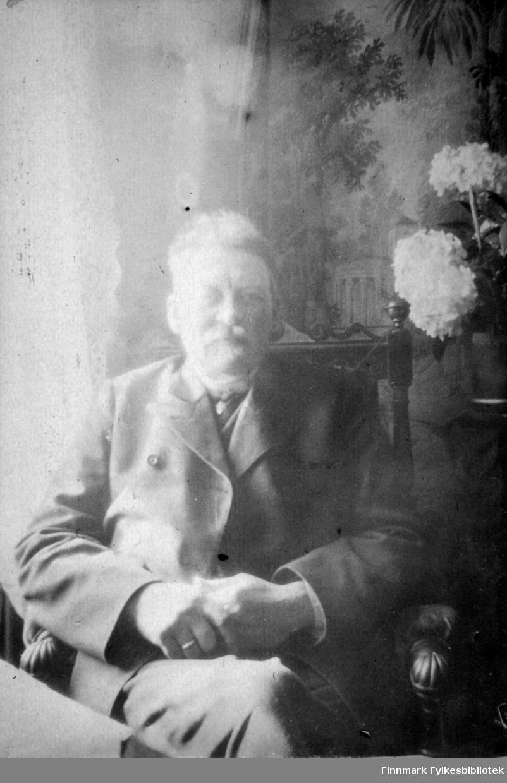 Arthur Buck sitter foran et bord. Stolen han sitter i har høy rygg med urskjæringer på stolpene og armlenene. Han har beina i kors og er iført dress og slips. På høyre hand har han en blank giftering. Et vindu til høyre for han har lyse, tynne gardiner og til venstre står en plante med to-tre store blomster. Bak han er et stort maleri eller en tapet som viser mye trær. Nede til venstre på bildet ses hjørnet av et bord med en lys duk på.